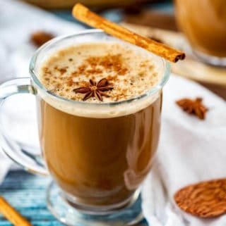 Photo of a Dirty Chai Latte in a glass mug garnished with ground cinnamon, a cinnamon stick, and a star anise.