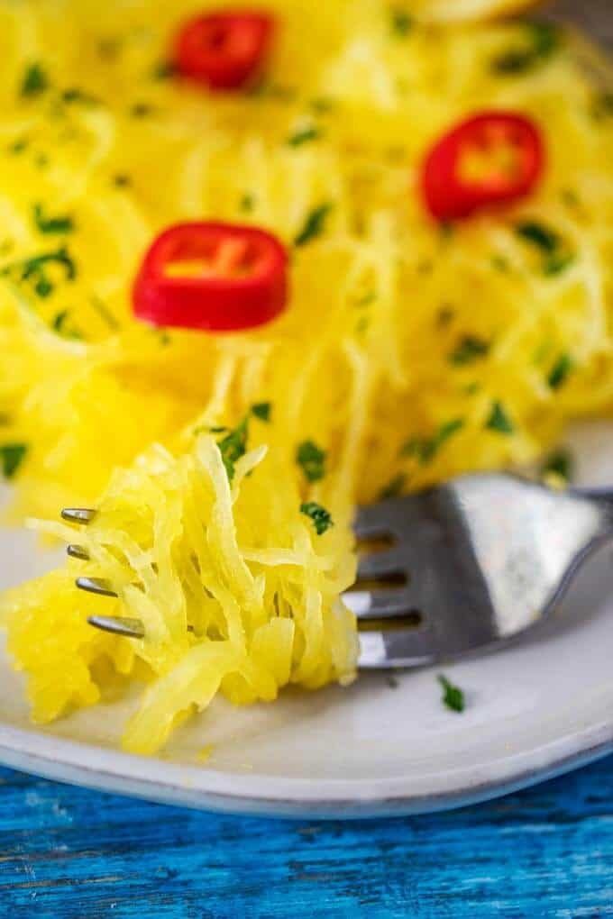 Close up photo of Instant Pot Spaghetti Squash on a fork garnished with parsley and hot peppers.