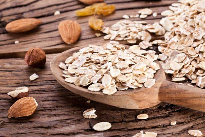 Photo of oats and almonds on a dark background.