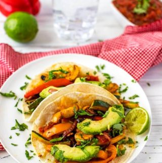Photo of vegetarian fajitas on a small white plate garnished with cilantro sitting on a white background.