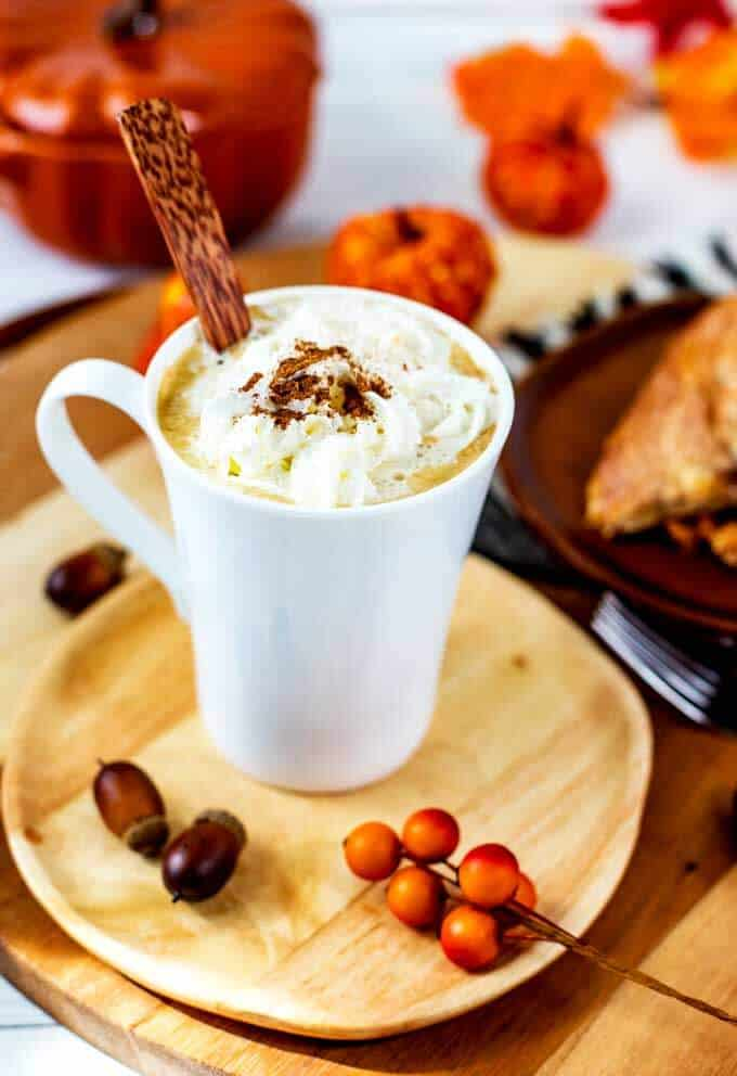 Photo of Starbucks Pumpkin Spice Coffee in a white mug with fall accessories surrounding it.