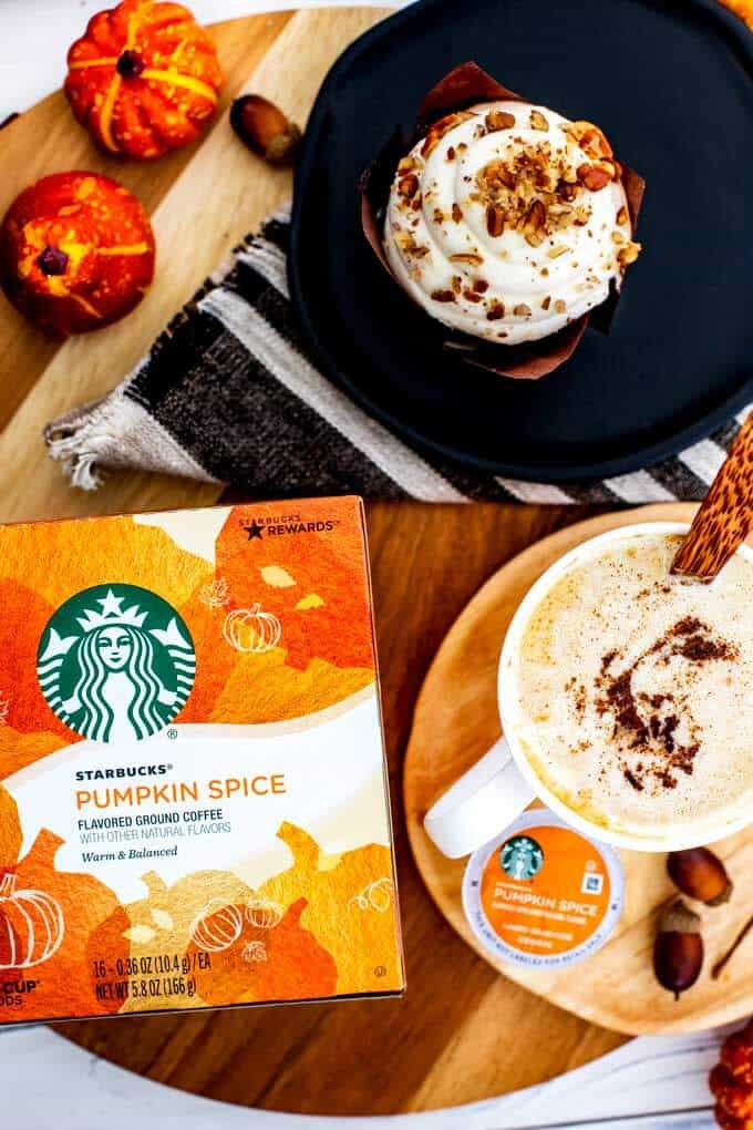 Overhead photo of a cup of Pumpkin Spice Coffee and a pastry with a box of Starbucks Pumpkin Spice coffee.