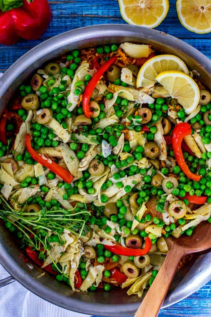 Photo of Vegetarian Paella in a skillet with a spoon garnished with lemon and parsley.