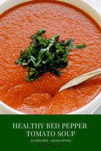 """Close up photo of Roasted Red Pepper Tomato Soup in a white bowl with the text """"Roasted Red Pepper Tomato Soup"""" in white against a green background below."""