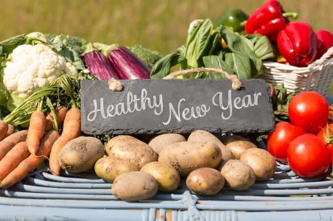 Photo of a sign that says Healthy New Year surrounded by produce.