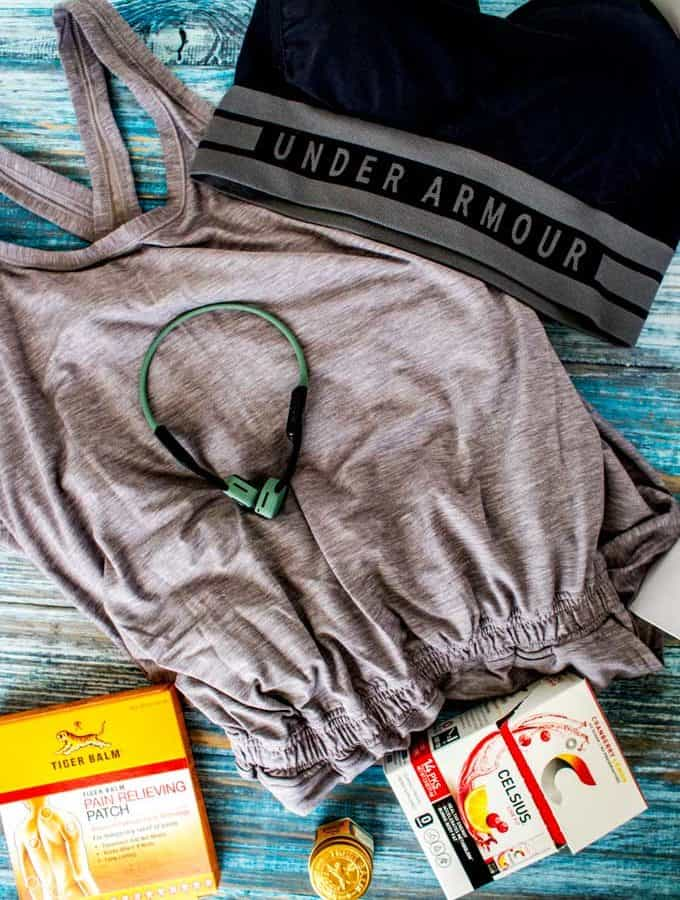 Photo of the contents of Babble Box Fitness - Seamless Bra, Athlete Recovery Jumpsuit, Open Ear Headphones, Celsius On-the-Go and Tiger Balm.