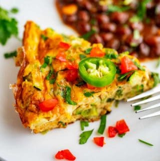 Close up photo of a zucchini frittata on a white plate garnished with jalapeno, tomato, and cilantro.