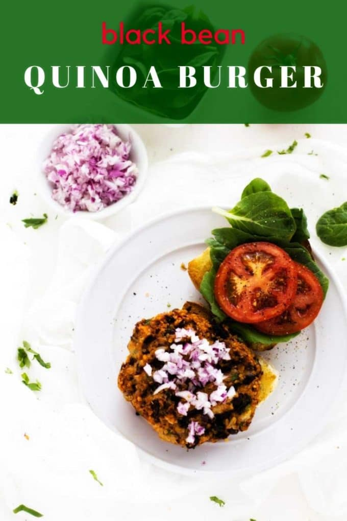 Photo of a Black Bean Quinoa Burger on a white plate against a white background with the recipe title written on a green text overlay above it.