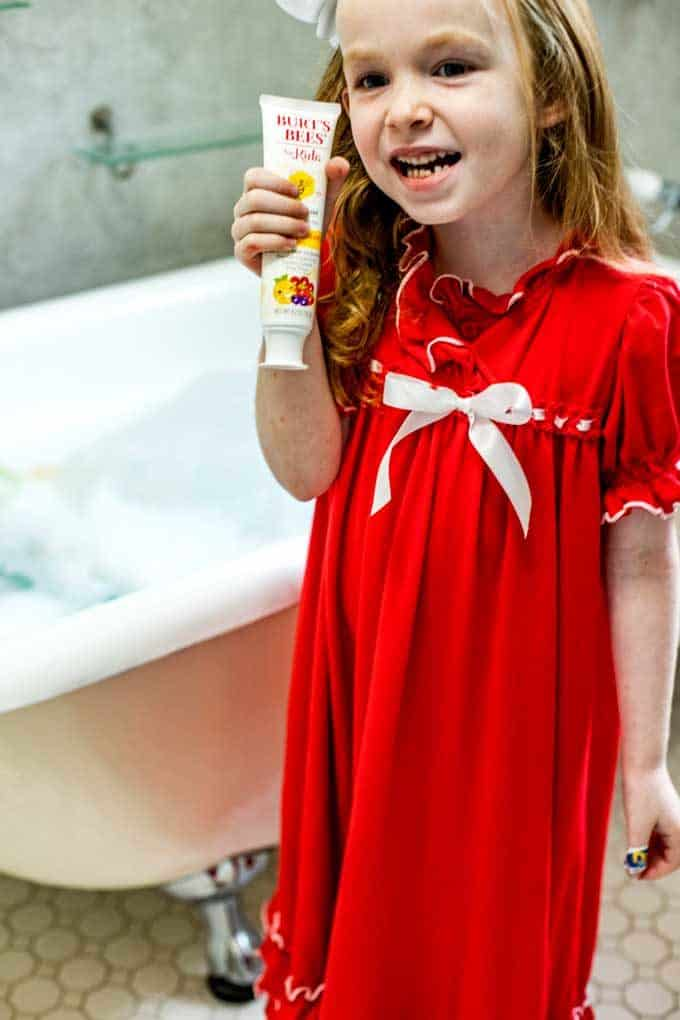 Photo of a 5 year old girl in a red nightgown holding Burt's Bees toothpaste standing beside a clawfoot tub.