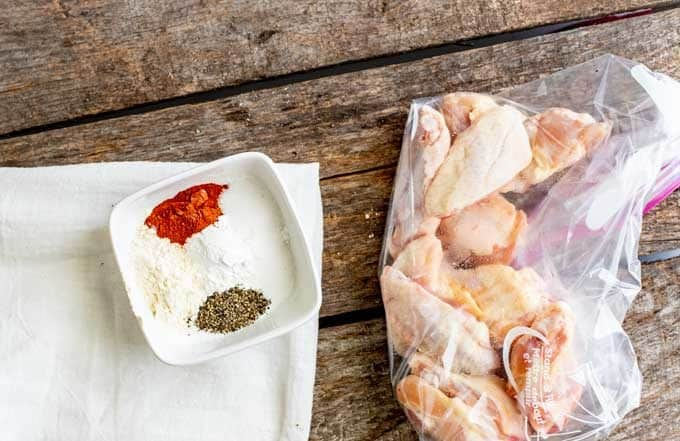 Seasoning mixture in a small white prep bowl sitting next to a zip top bag of chicken wings.
