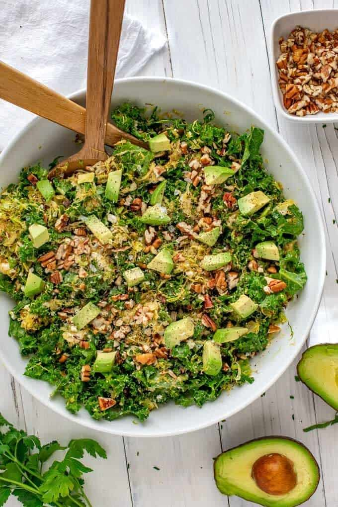 Overhead photo of Kale and Brussels Sprouts salad in a large white bowl with salad mixers in it and avocado, pecans and parsley sitting by it.