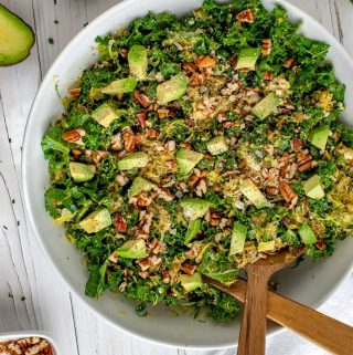 Overhead square photo of a Kale Brussels Sprouts Salad in a white bowl with serving utensils.