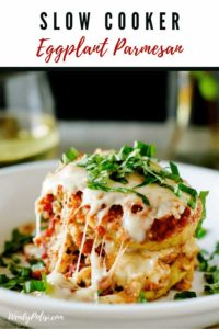 Photo of Eggplant Parmesan on a white plate garnished with basil sitting on a wooden background with the text Slow Cooker Eggplant Parmesan above it.