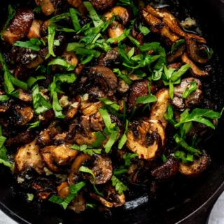 Overhead photo of Air Fryer Mushrooms in a small cast iron skillet garnished with parsley.