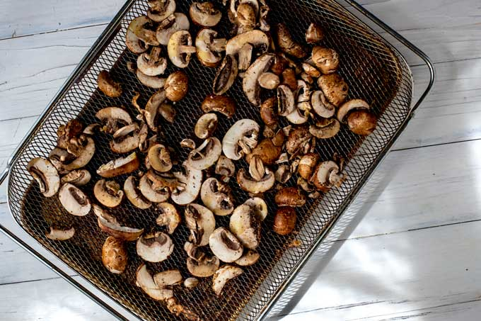 Seasoned mushrooms in a single layer of an air fryer basket.