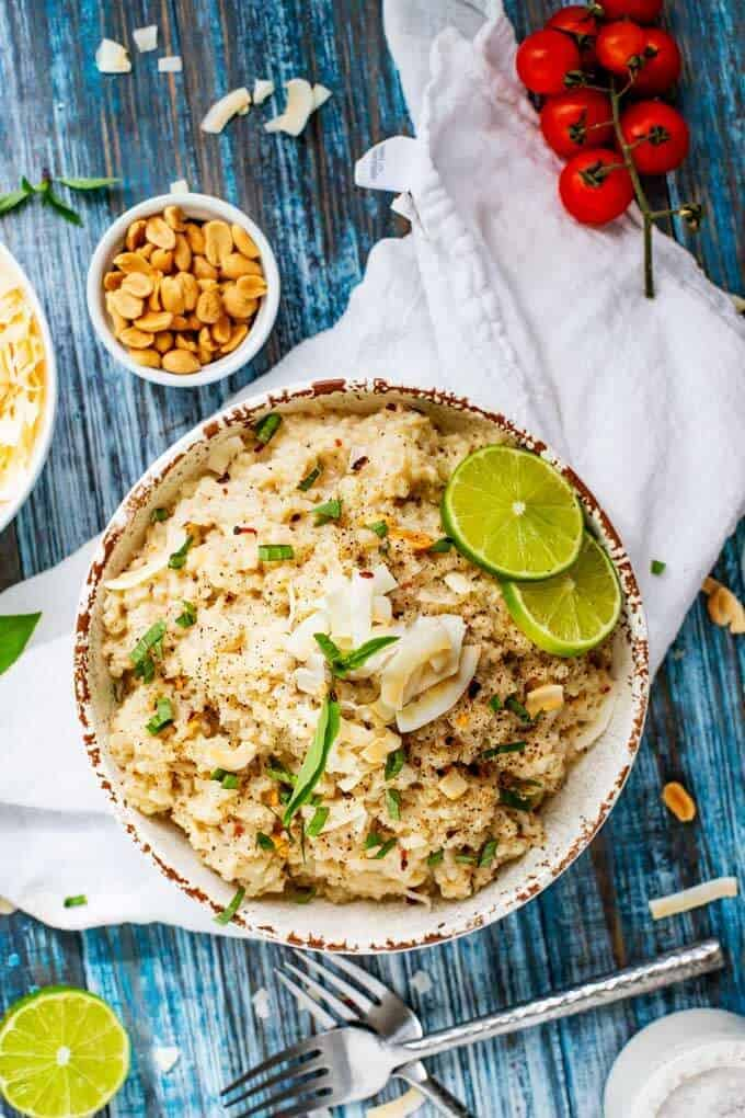 Overhead photo of Coconut Cauli-Rice that is sitting on a white napkin with two spoons crossed over next to it and fresh cut limes.