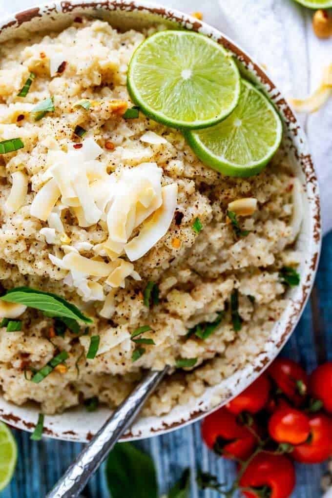 Close up overhead photo of Coconut Cauliflower Rice in a rustic white bowl with coconut on top and vine ripe cherry tomatoes sitting next to it.