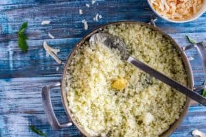 Photo of garlic being added to a skillet of cauli-rice that sits on a blue background.