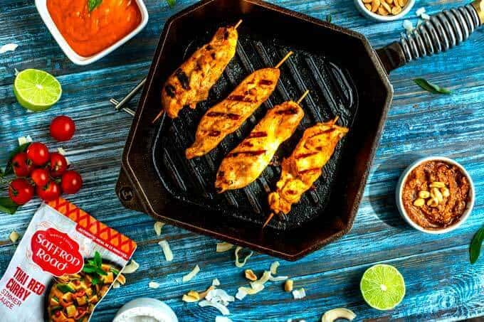 Photo of chicken strips on skewers in a cast iron skillet sitting on a blue background surrounded by sauce, pecans, coconut, tomato, and lime.
