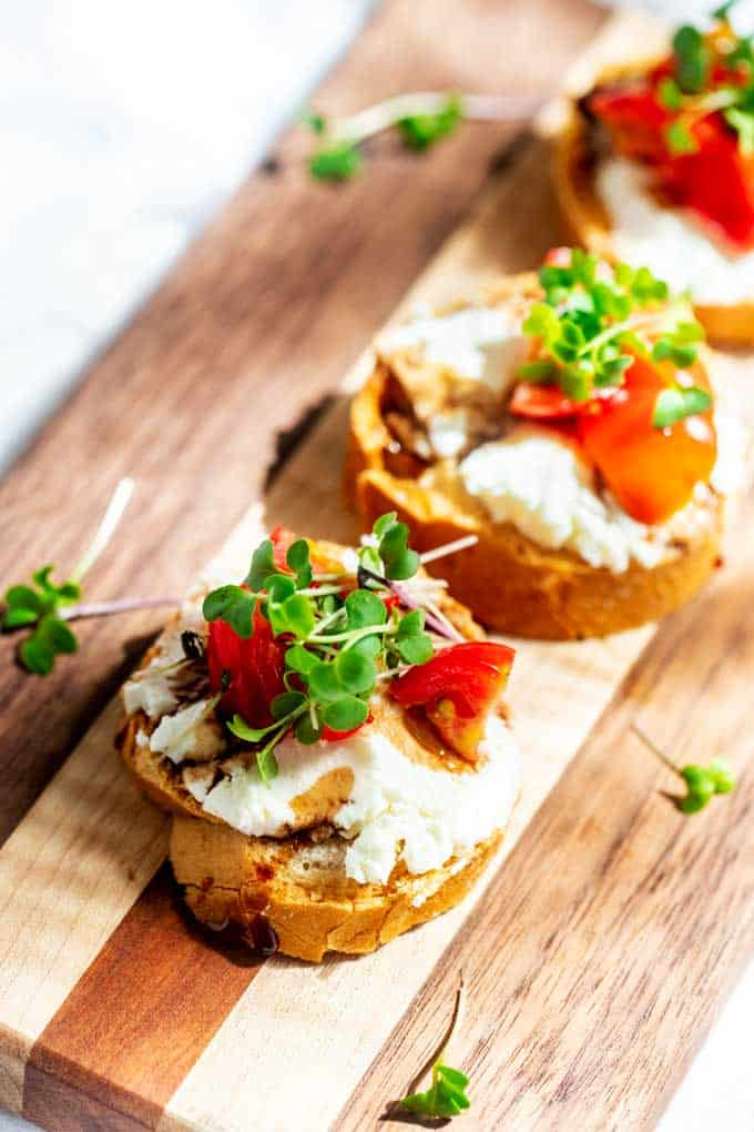 Close up photo of a small bread round topped with goat cheese, tomatoes, balsamic reduction and microgreens sitting on a wooden cutting board.