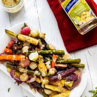Overhead photo of Roasted Spring Vegetables on a white platter drizzled with a mustard wine dressing. There is a bottle of Holland House White Cooking Wine sitting on a red napkin next to it.