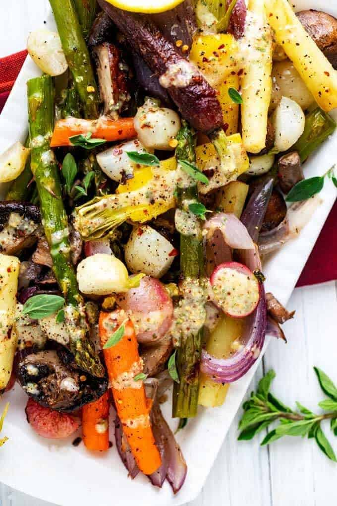 Close up photo of Roasted Spring Vegetables on a white platter garnished with thyme and drizzled with a mustard vinaigrette.