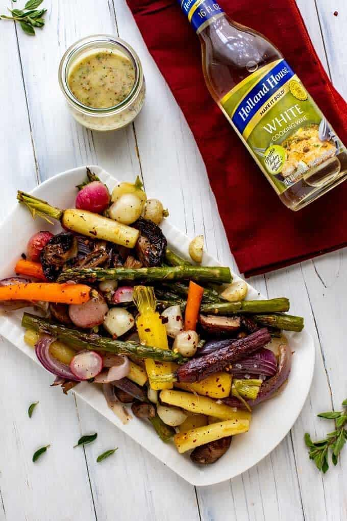 Overhead photo of Roasted Spring Vegetables on a white platter sitting on a wooden white background with thyme next to it and a bottle of Holland House White Cooking Wine.