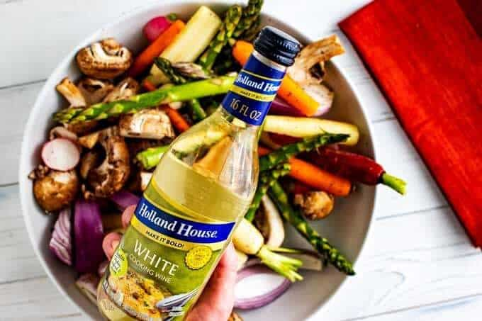 Photo of Holland House White Cooking Wine over a bowl of spring vegetables.