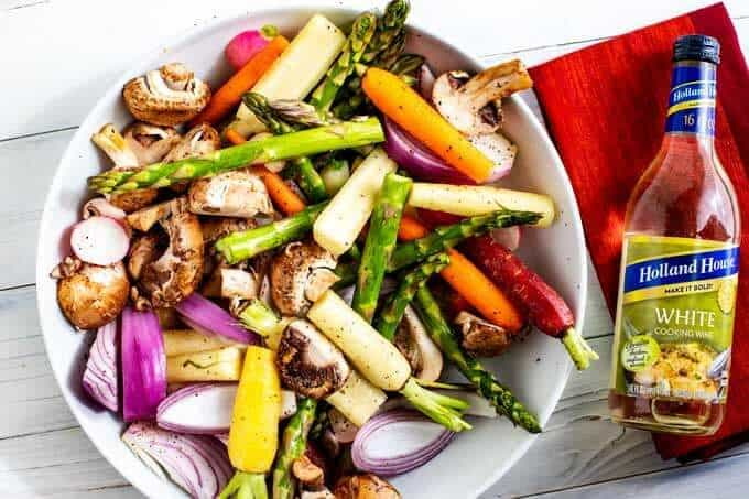 White bowl with asparagus, carrots, mushrooms, onions, and radishes mixed together and a bottle of white cooking wine sitting next to it.