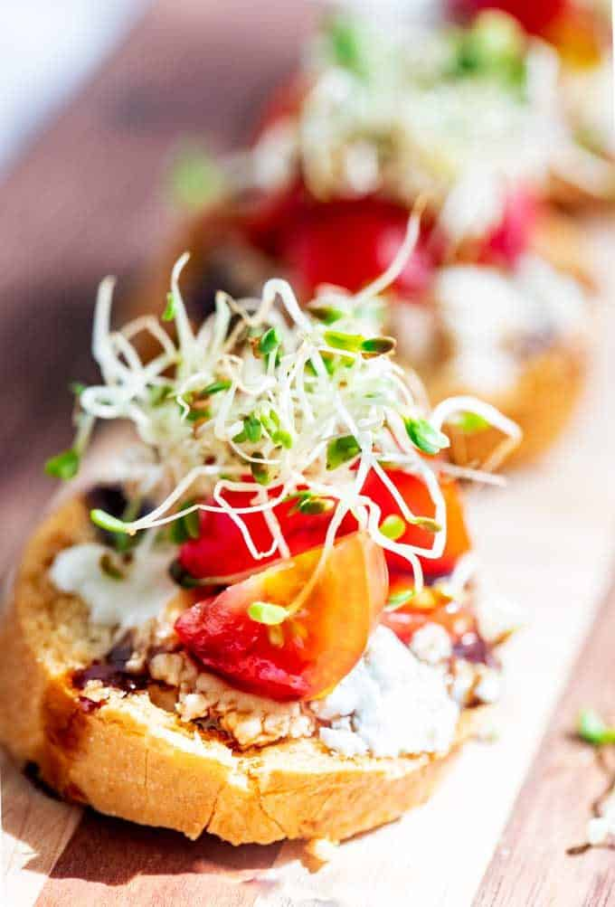 Close up photo of a small bread rount topped with goat cheese, balasmic, tomatoes and sprouts.