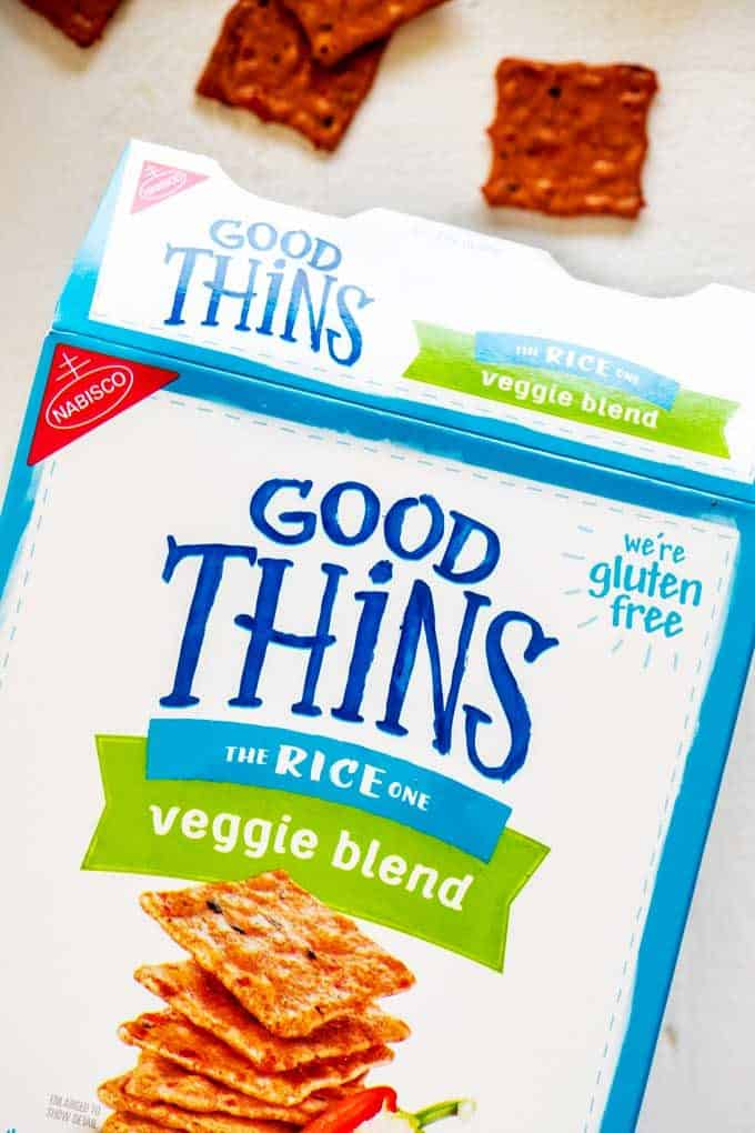 Close up photo of a box of good thins crackers open on its side against a white background with crackers scattered above it.