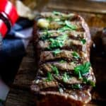 Close up photo of a grilled steak on a wooden cutting board garnished with parsley.