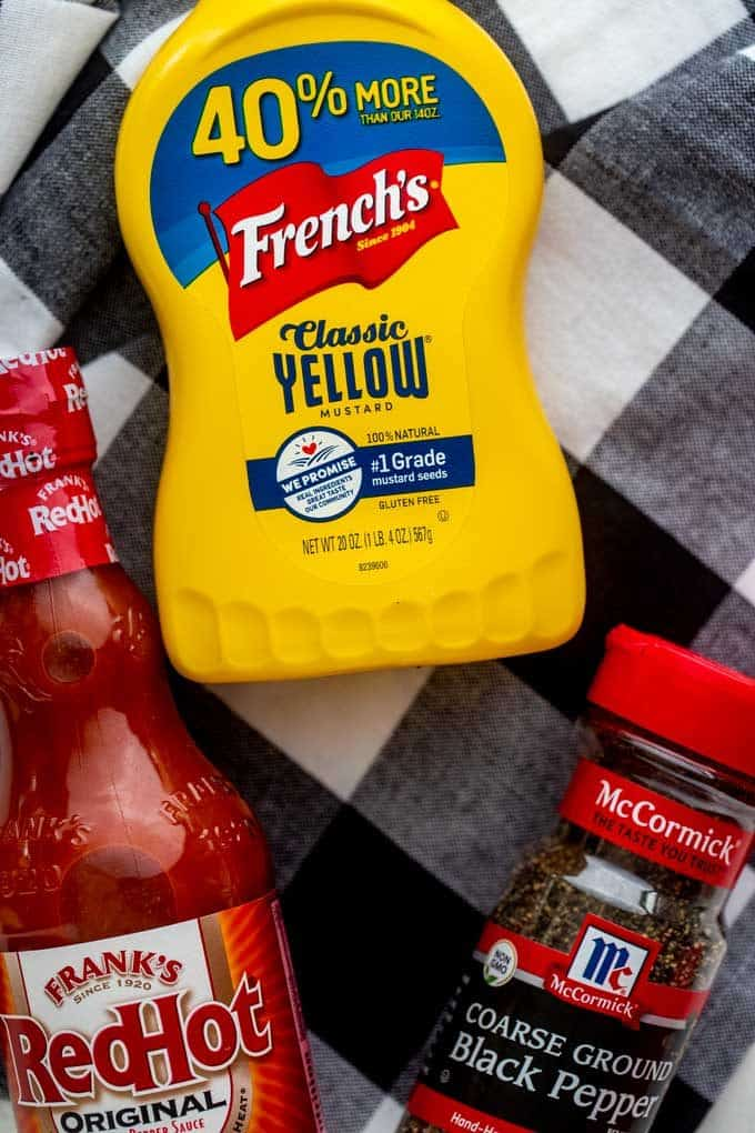 Photo of Franks Red Hot, French's Mustard, and McCormick Black pepper against a black checkered napkin.