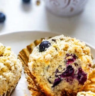 Close up photo of a blueberry quinoa muffin with two other muffins beside it sitting on a white plate with a white mug behind it.