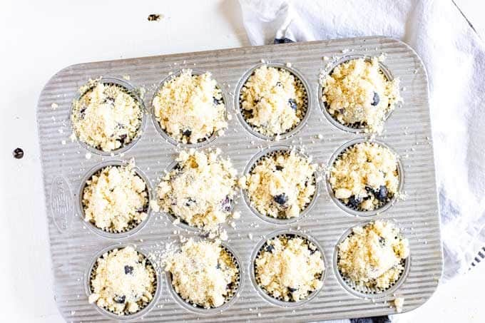 Photo of a muffin tin with blueberry quinoa muffin batter that has been topped with a crumbly topping.