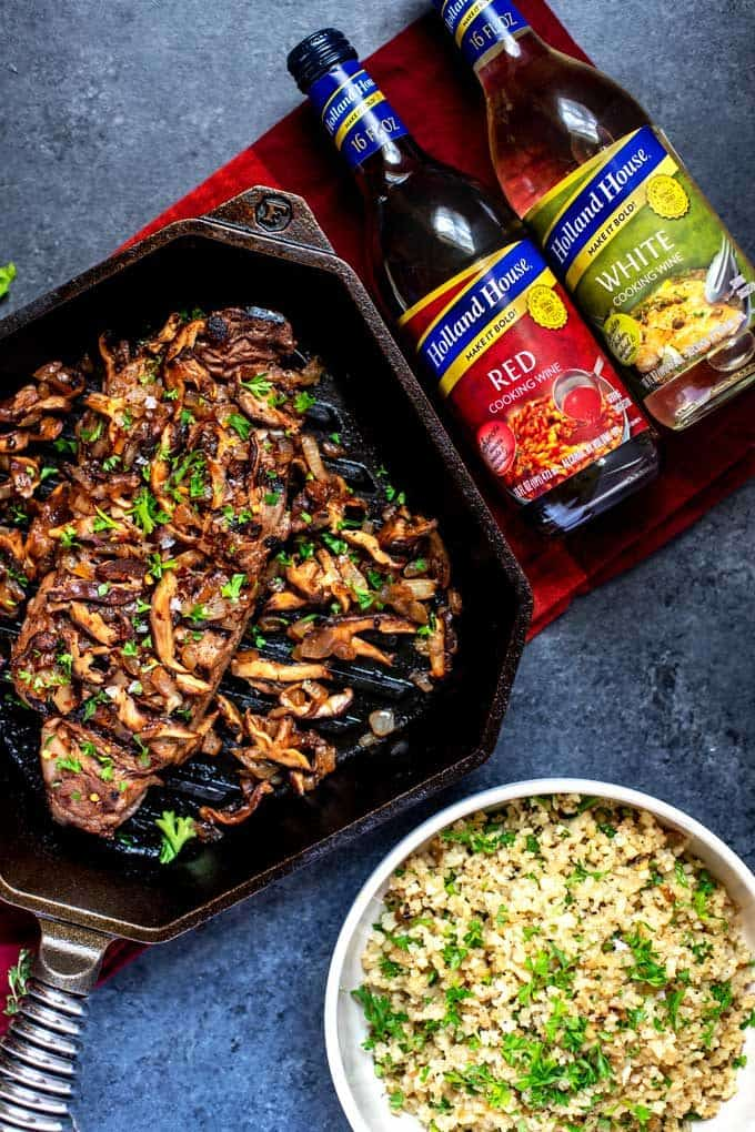 Overhead photo of a cast iron grill pan with Steak with Mushrooms and onions with a bowl of cauliflower rice sitting next to it and a bottle of red cooking wine and white cooking wine.