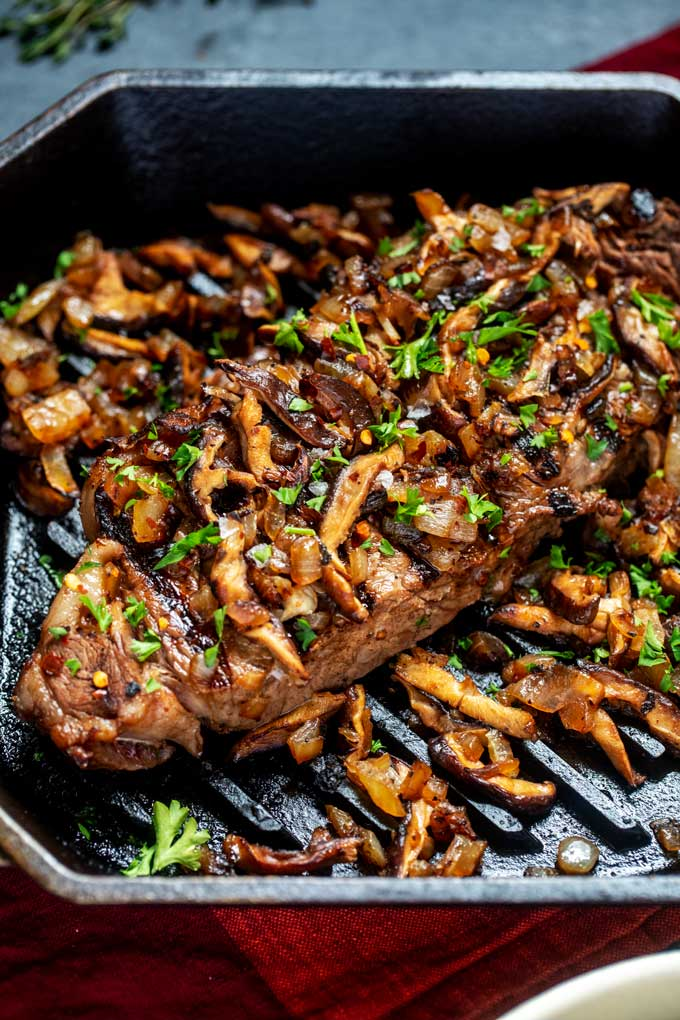 Close up photo of a grilled steak with mushrooms.