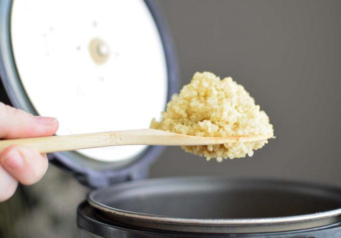 Photo of a spoonful of quinoa being lifted from a rice cooker.