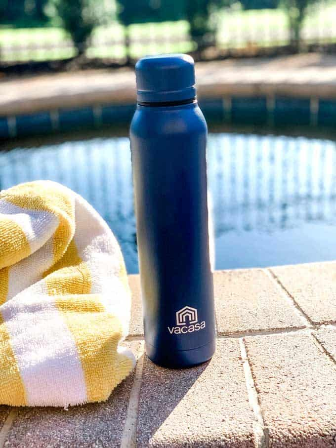 Photo of a blue water bottle that says Vacasa sitting by a pool.
