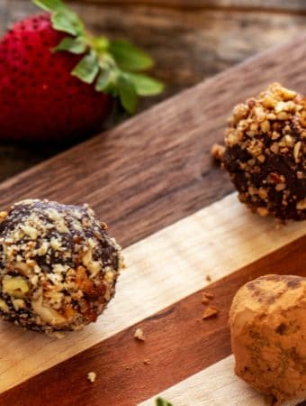 Photo of three gluten free truffles on a wooden cutting board with a strawberry next to it.