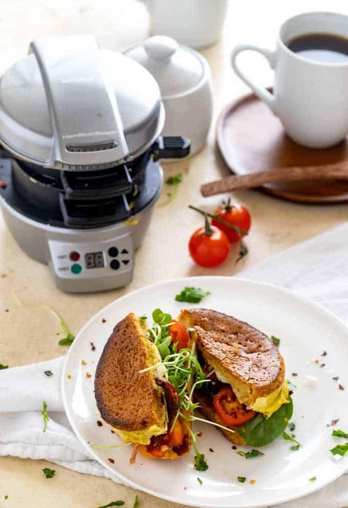 Photo of a gluten free breakfast sandwich on a white plate with a breakfast sandwich maker behind it.