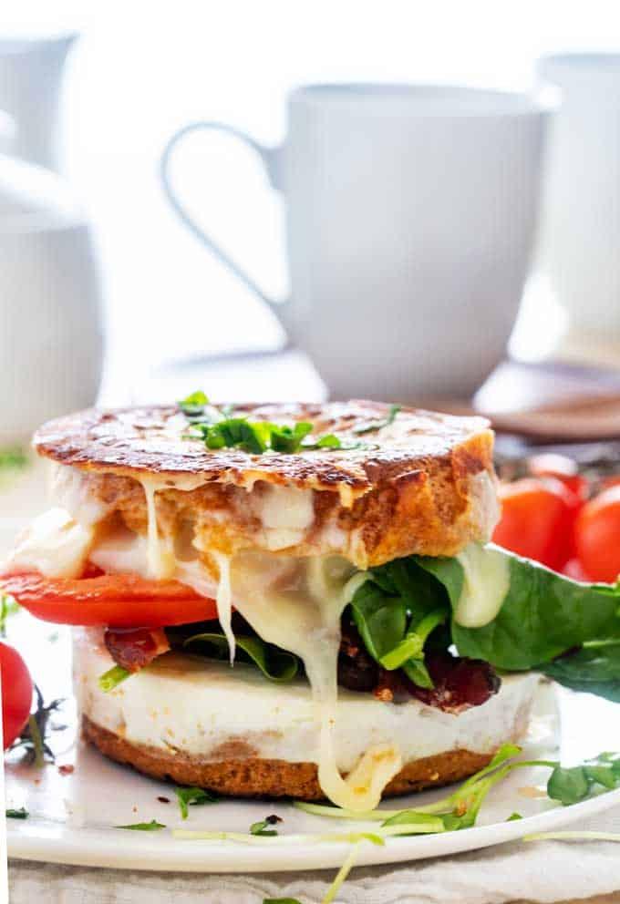 Side photo of a gluten free breakfast sandwich on a white plate.