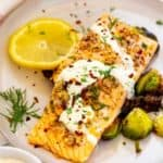 Square image of garlic salmon drizzled in a lemon dill sauce and garnished with dill.