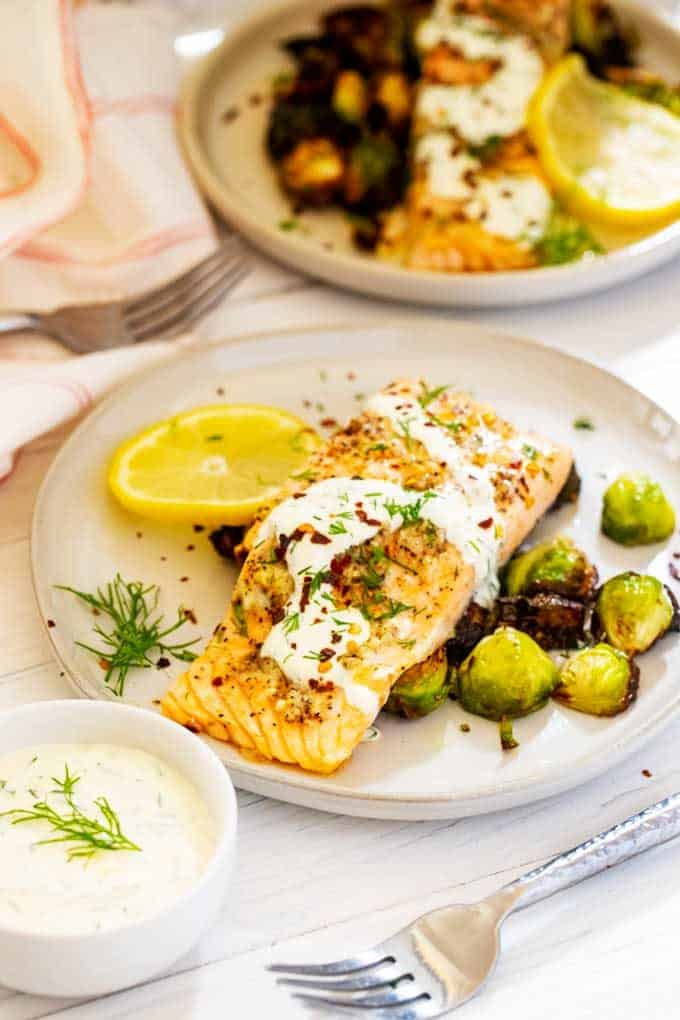 Photo of two plates of Garlic Salmon with a bowl of lemon dill sauce next to the front one.