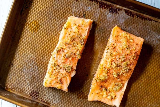 Photo of two garlic seasoned pieces of salmon ready to go in the oven.