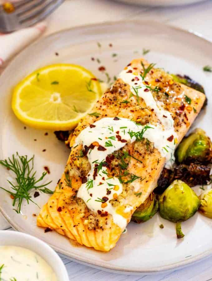 Overhead photo of Garlic Salmon on a bed of Brussels Sprouts garnished drizzled with a lemon dill sauce and garnished with dill.