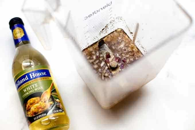 Photo of a blender with a white wine dressing in it and a bottle of Holland House white cooking wine.