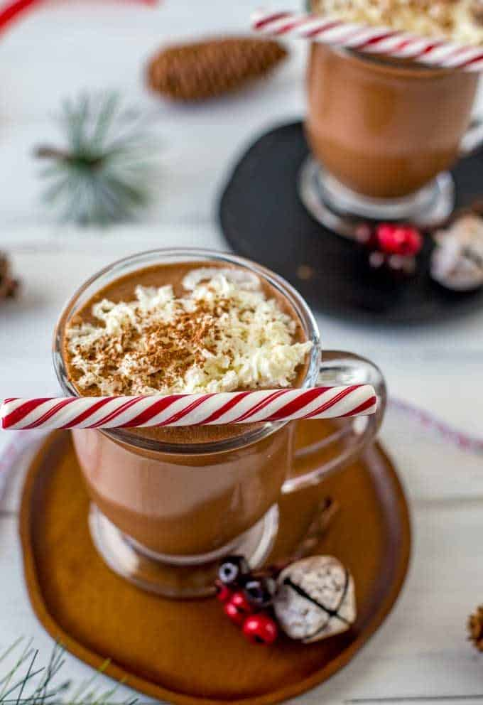 Photo of two glasses of Crock Pot Hot Chocolate with whipped cream and a mint stick on top.