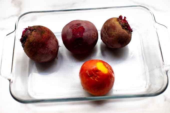 Photo of a baking dish with four raw beets.