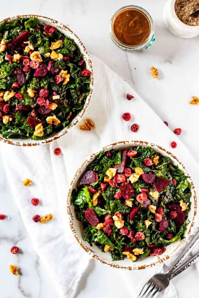 Overhead photo of two rustic bowls with Kale Beet Salad on a white background.